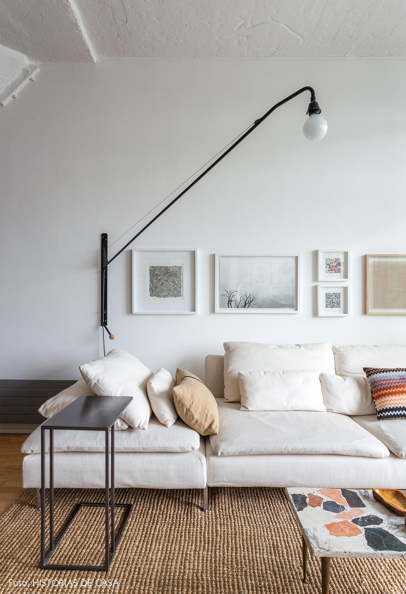 Sala com tons neutros, sofá bege e quadros