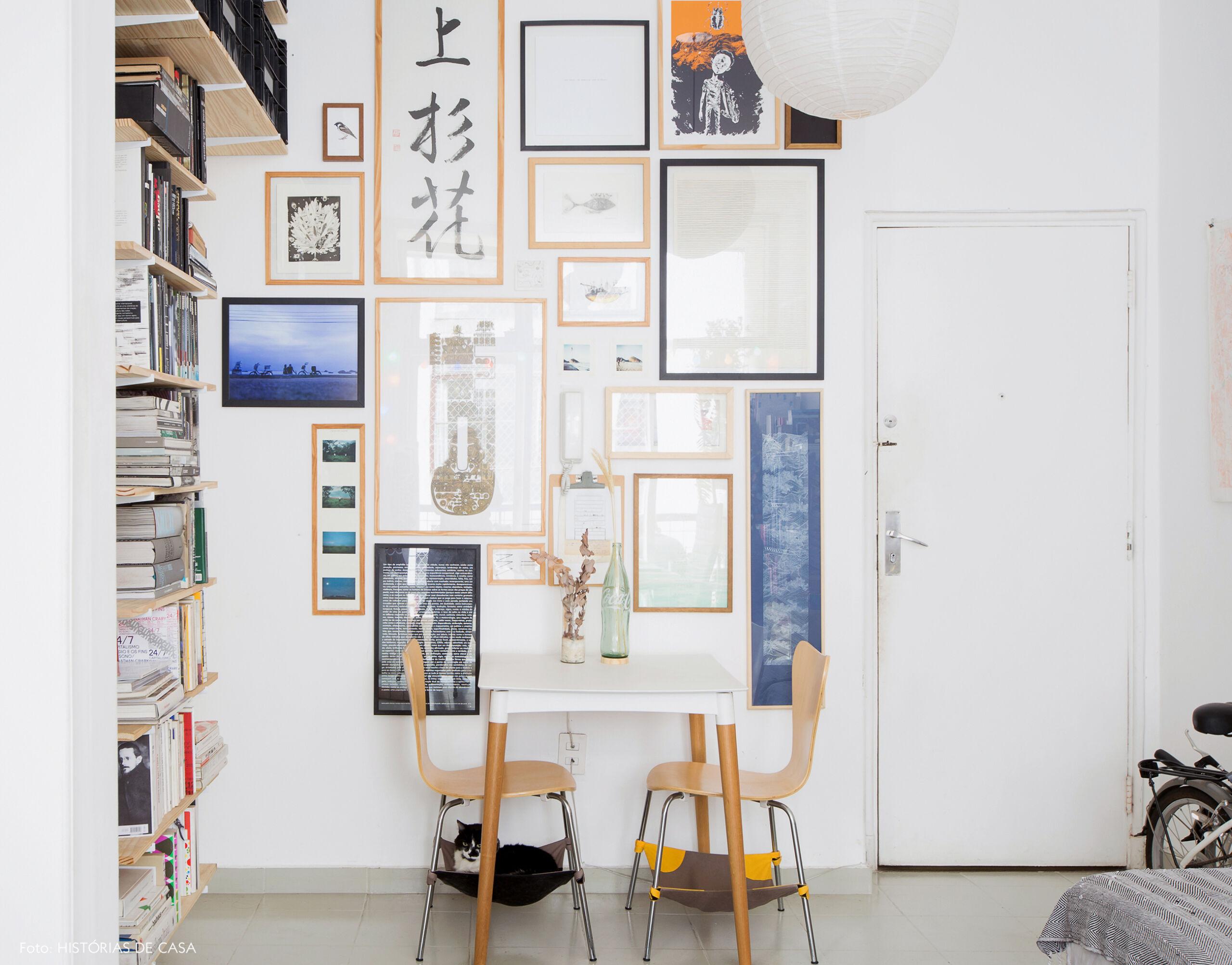 Apartamento pequeno com sala de jantar e parede de quadros