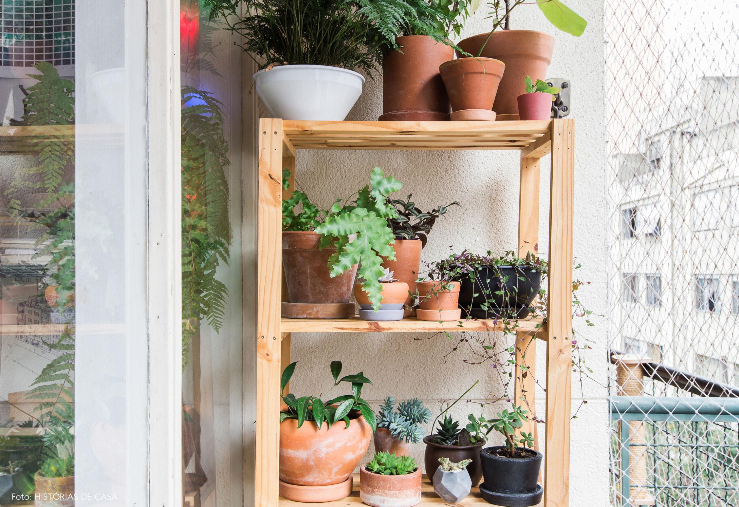 Estante de madeira na varanda com plantas