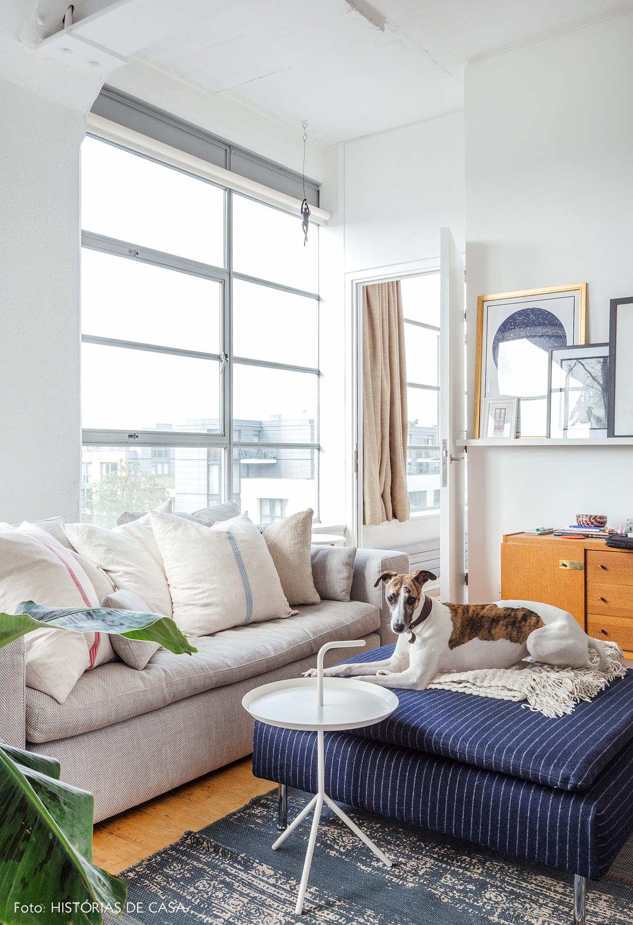 Sala com sofá bege, pufe azul e móveis vintage