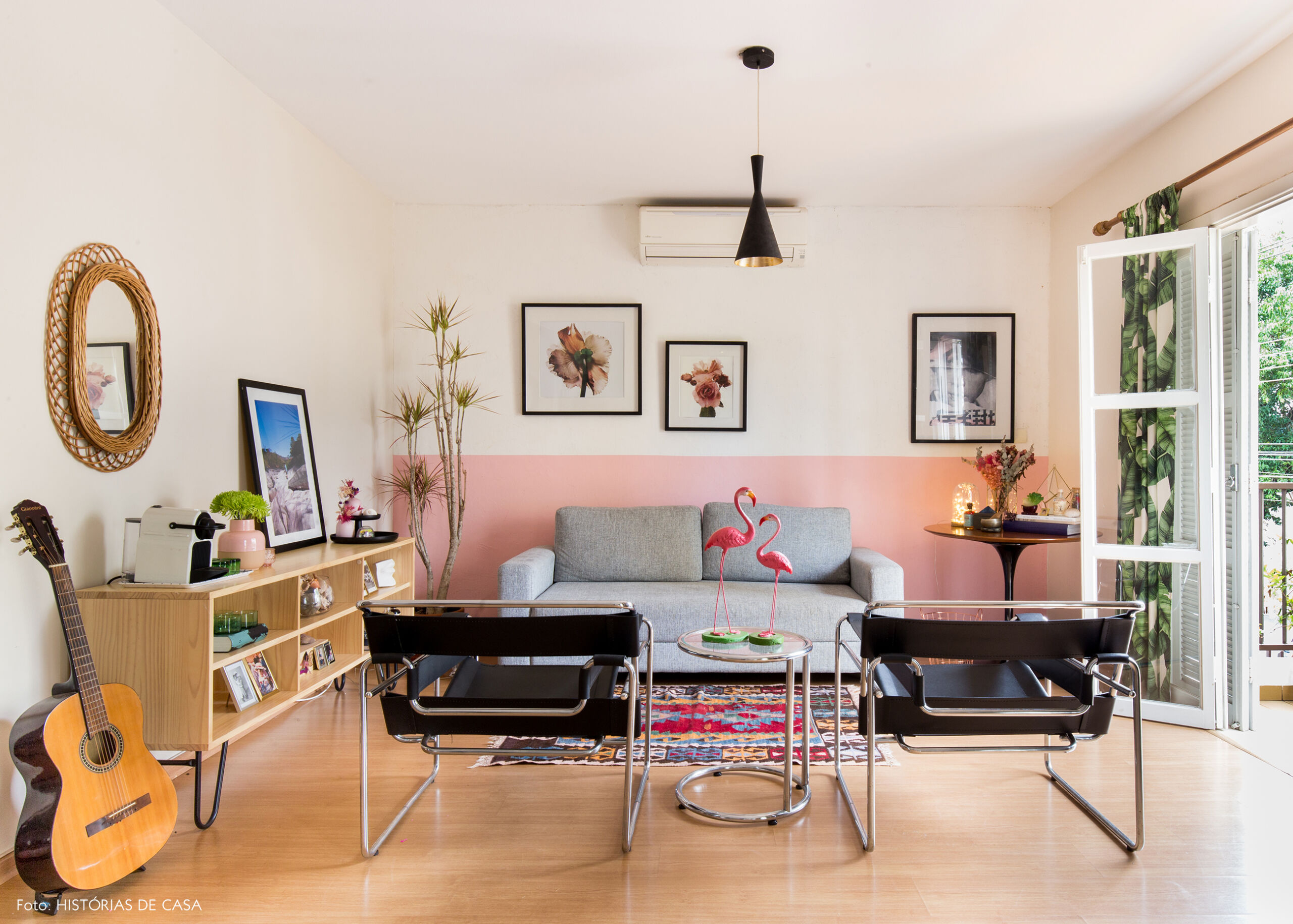 Sala com meia parede pintada de rosa e sofá cinza