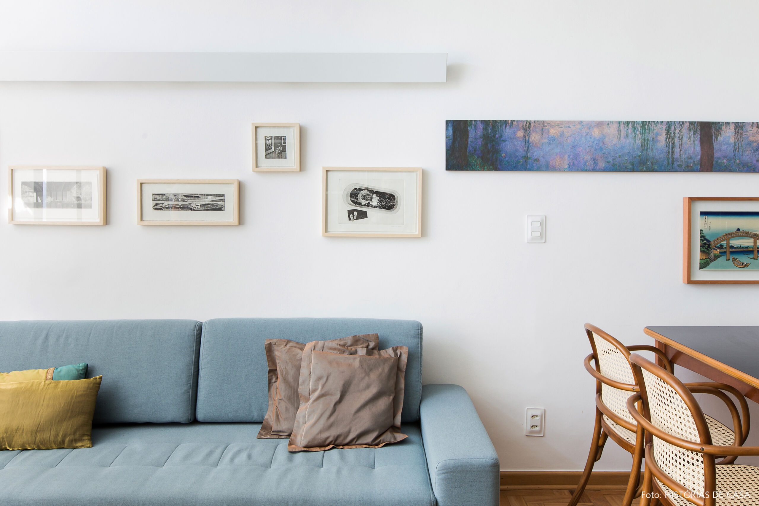 Sofá azul claro com quadros na parede