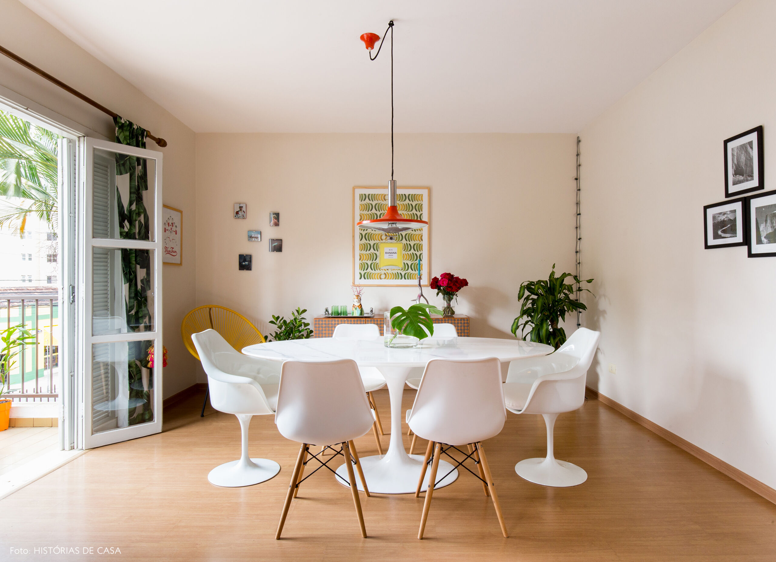 Sala de jantar com mesa Saarinen branca e pendente vintage