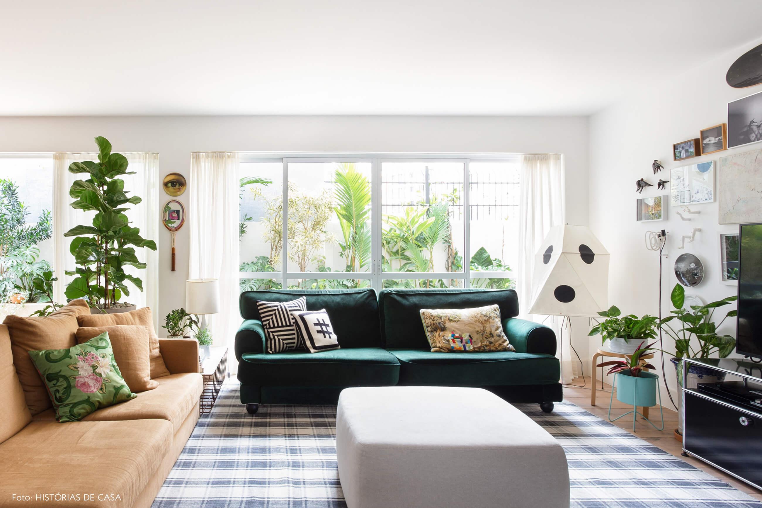 Sala com sofá de veludo verde e pufe cinza