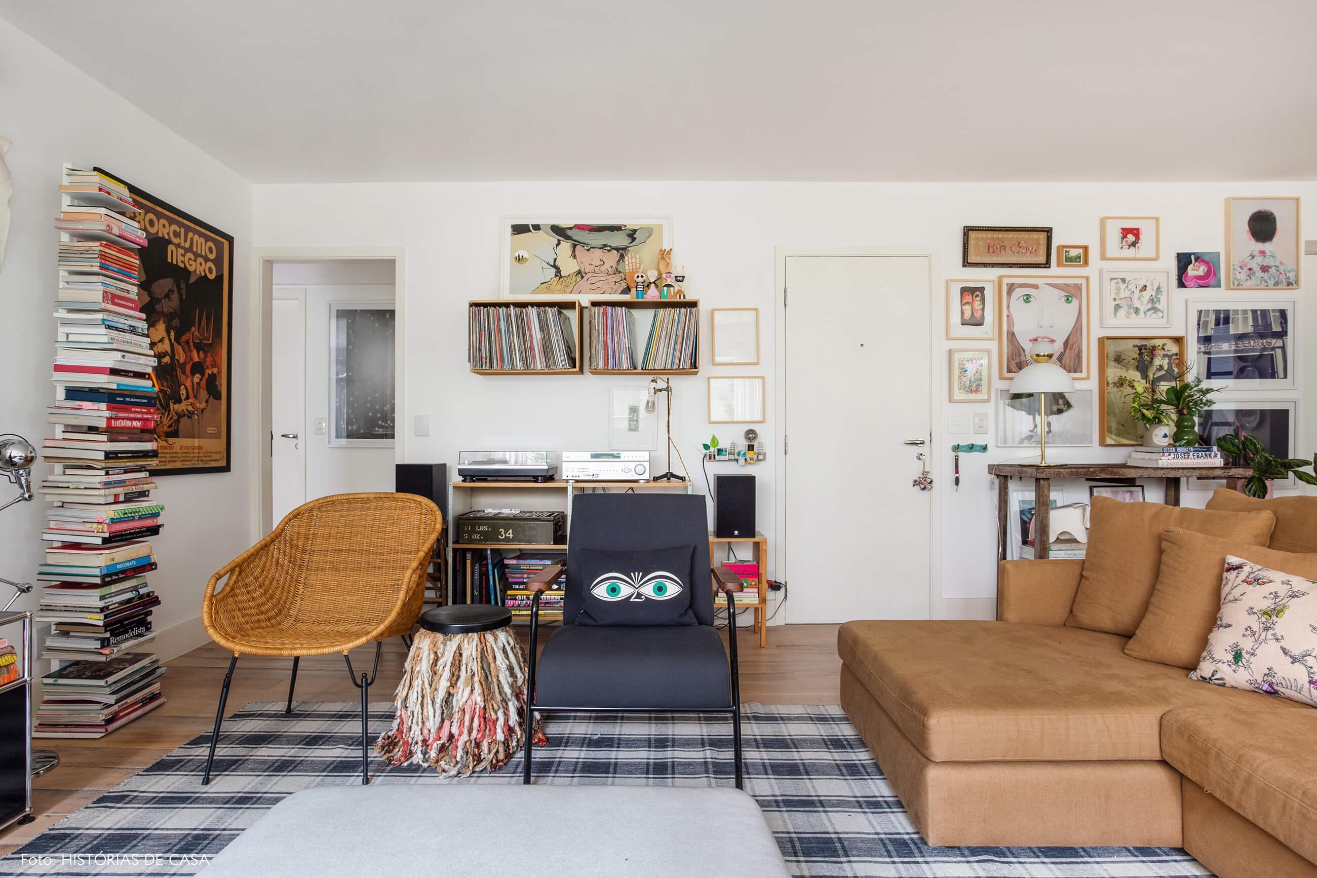 Sala com poltrona de vime e tapete preto e branco