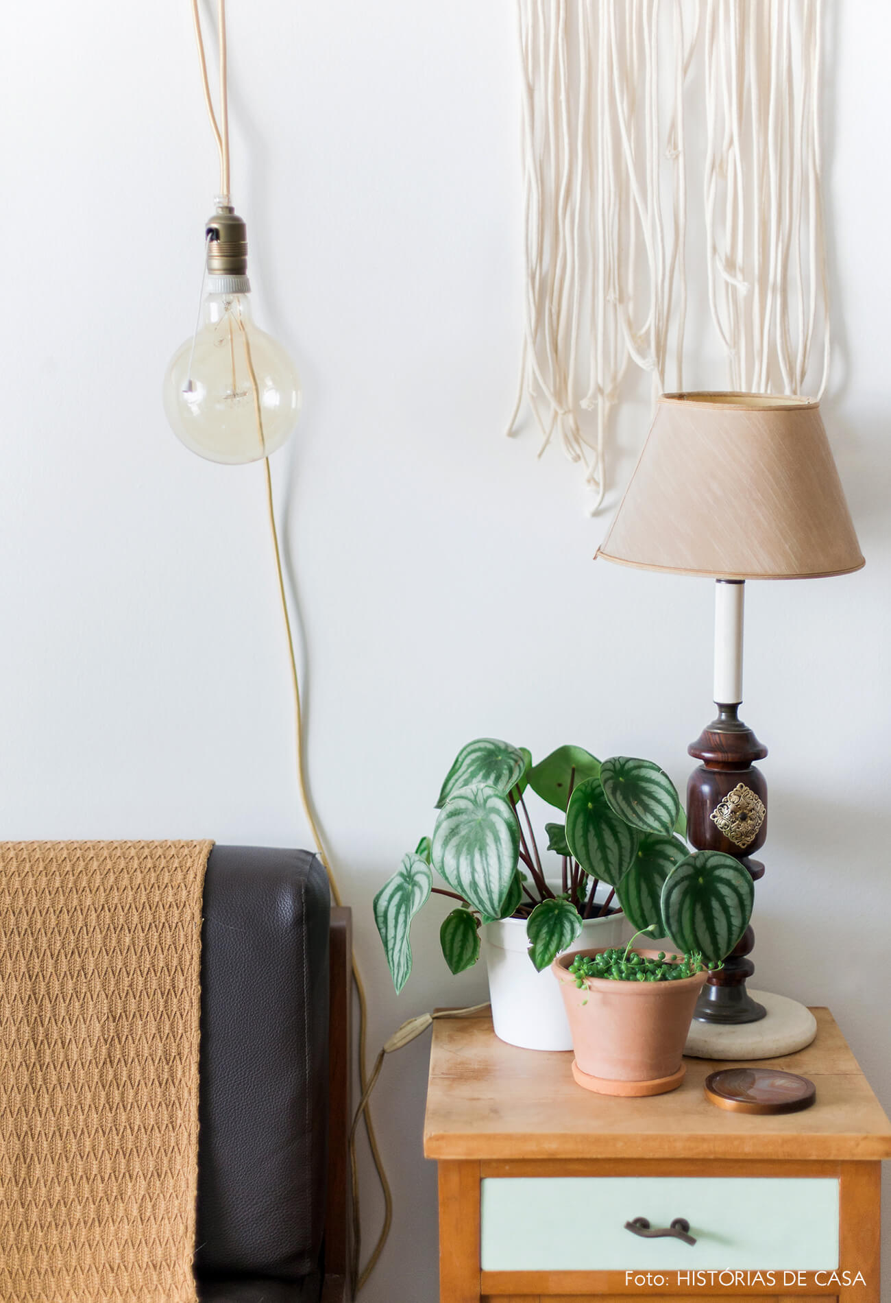 Mesa lateral com plantas e hanger de macramê na parede