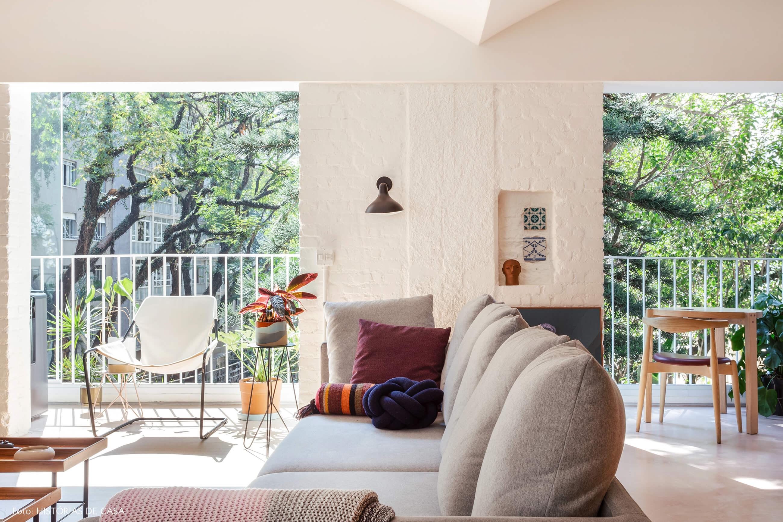Sofá cinza e parede de tijolinhos em apartamento