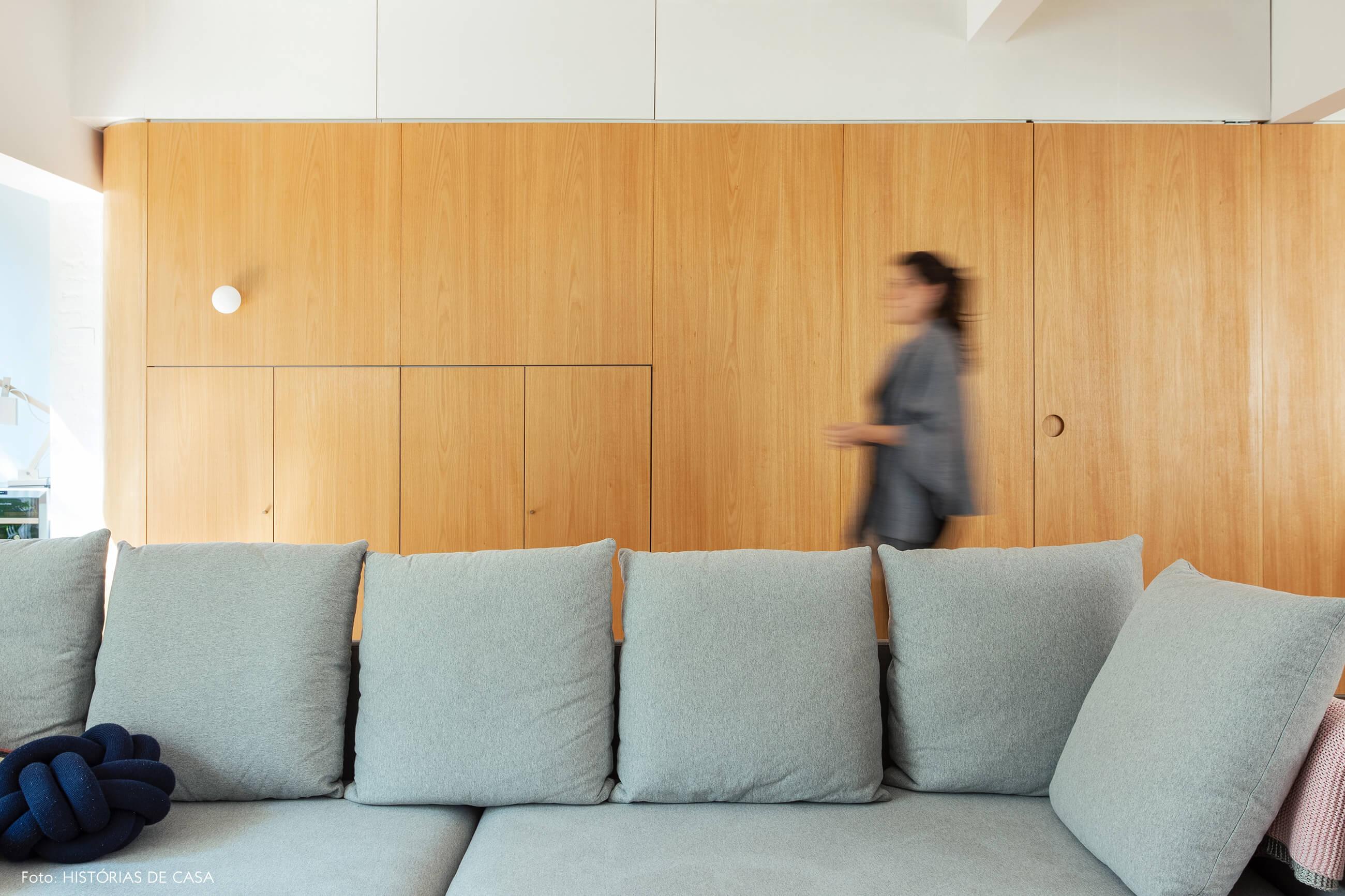 Sofá cinza neutro com painel de marcenaria ao fundo