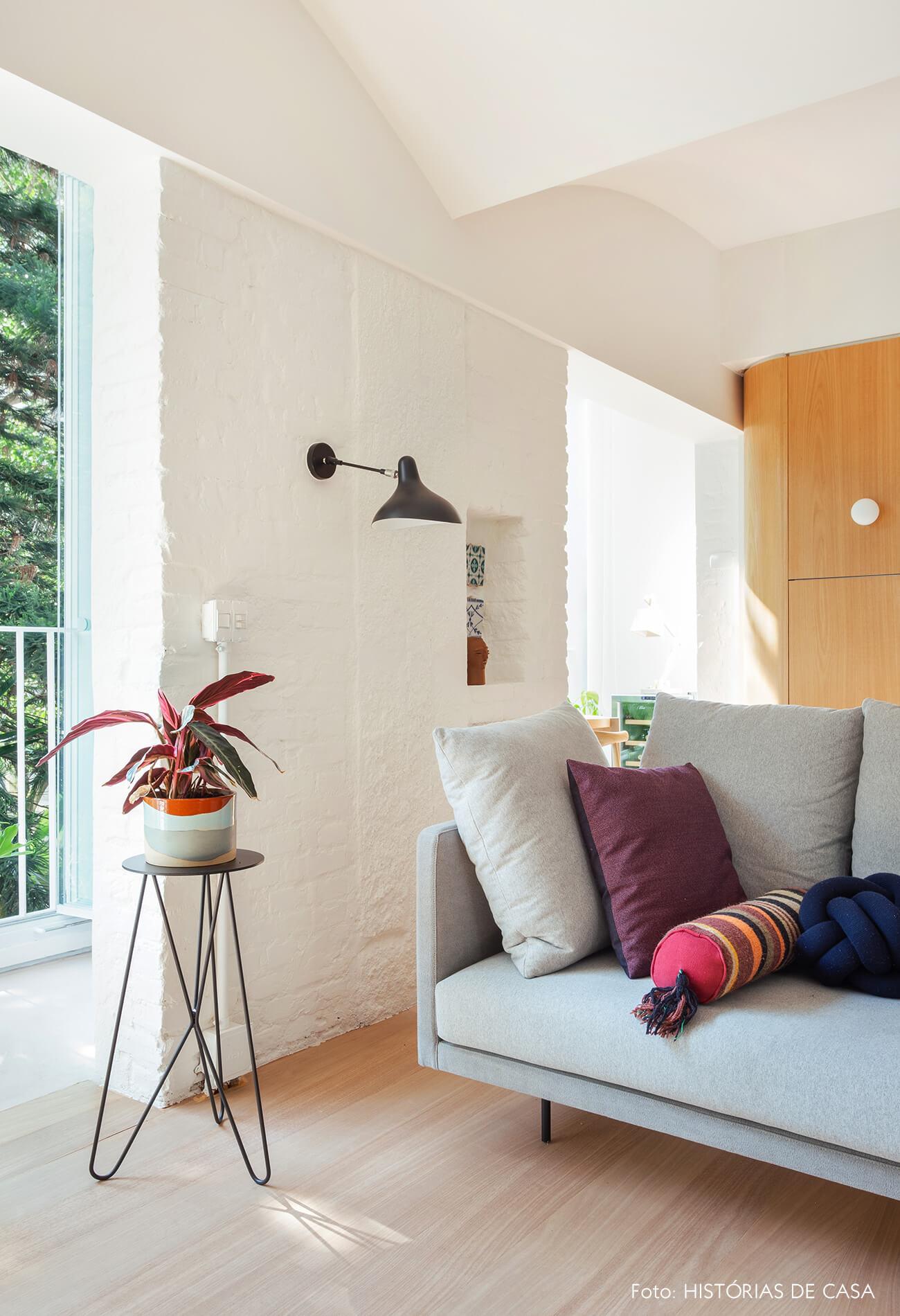 Sofá cinza e suporte com plantas em sala reformada