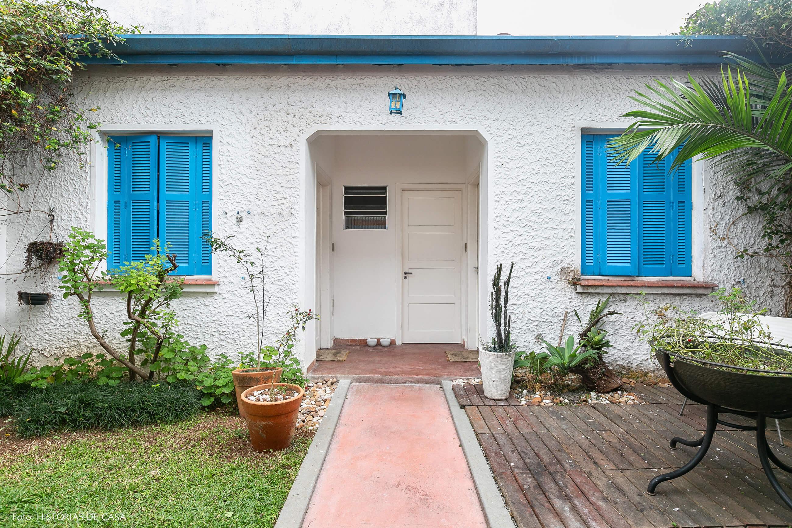 Quintal de casa com janelas pintadas de azul