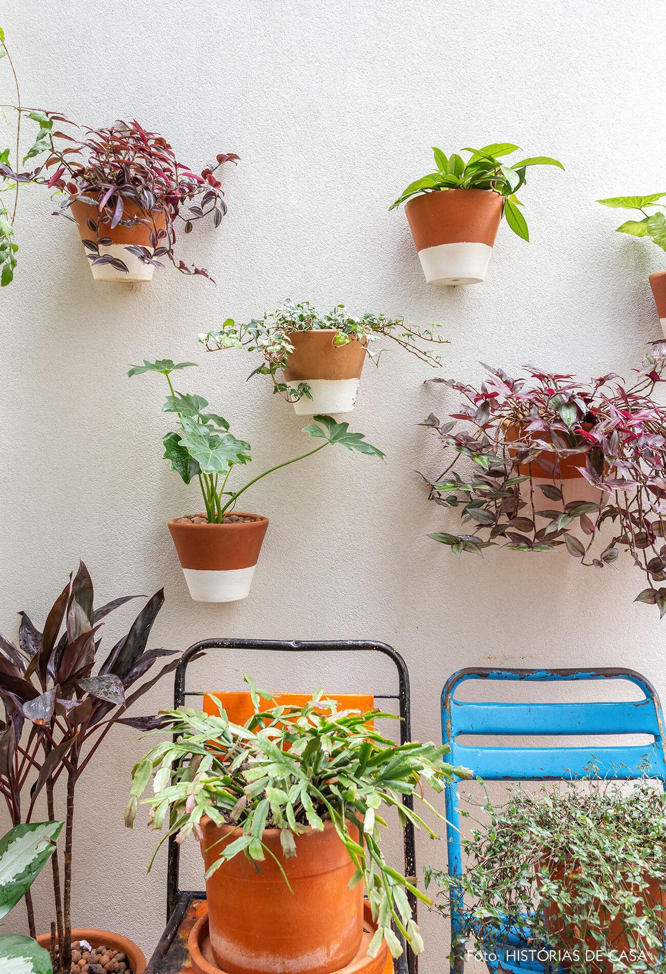 Jardim com muitas plantas e vasos na parede