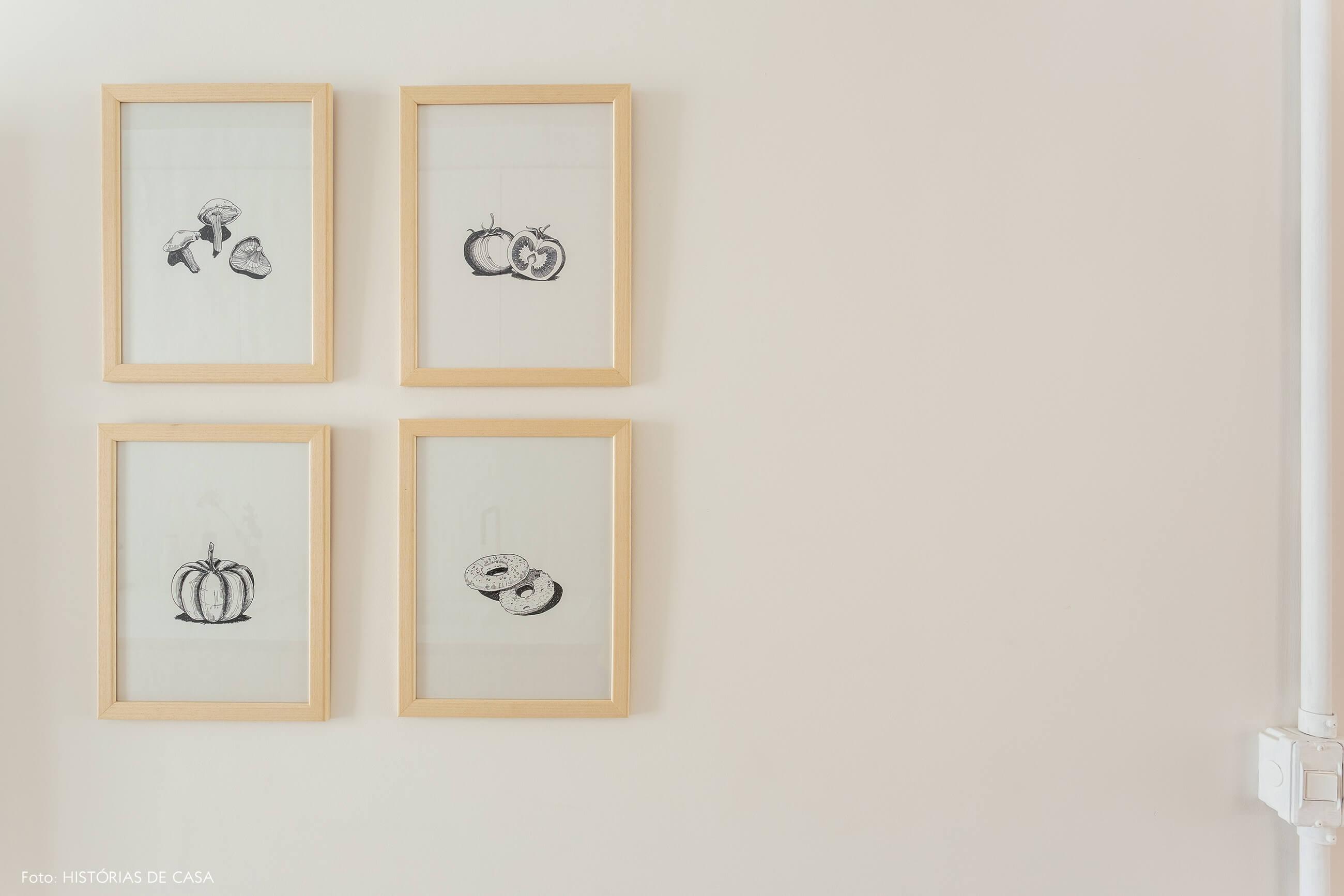 Gravuras em preto e branco na parede da cozinha