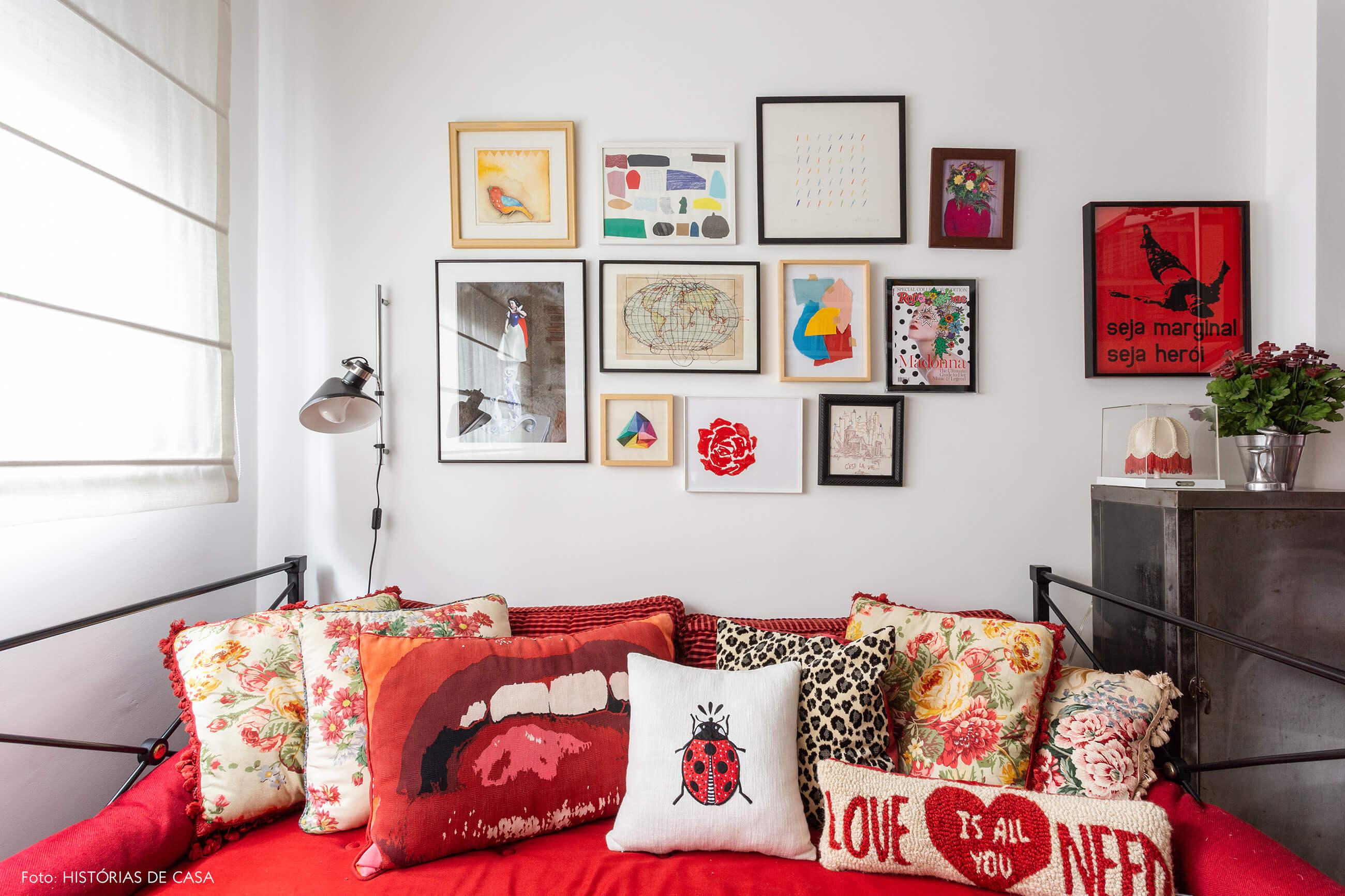Escritório com parede de quadros coloridos e sofá