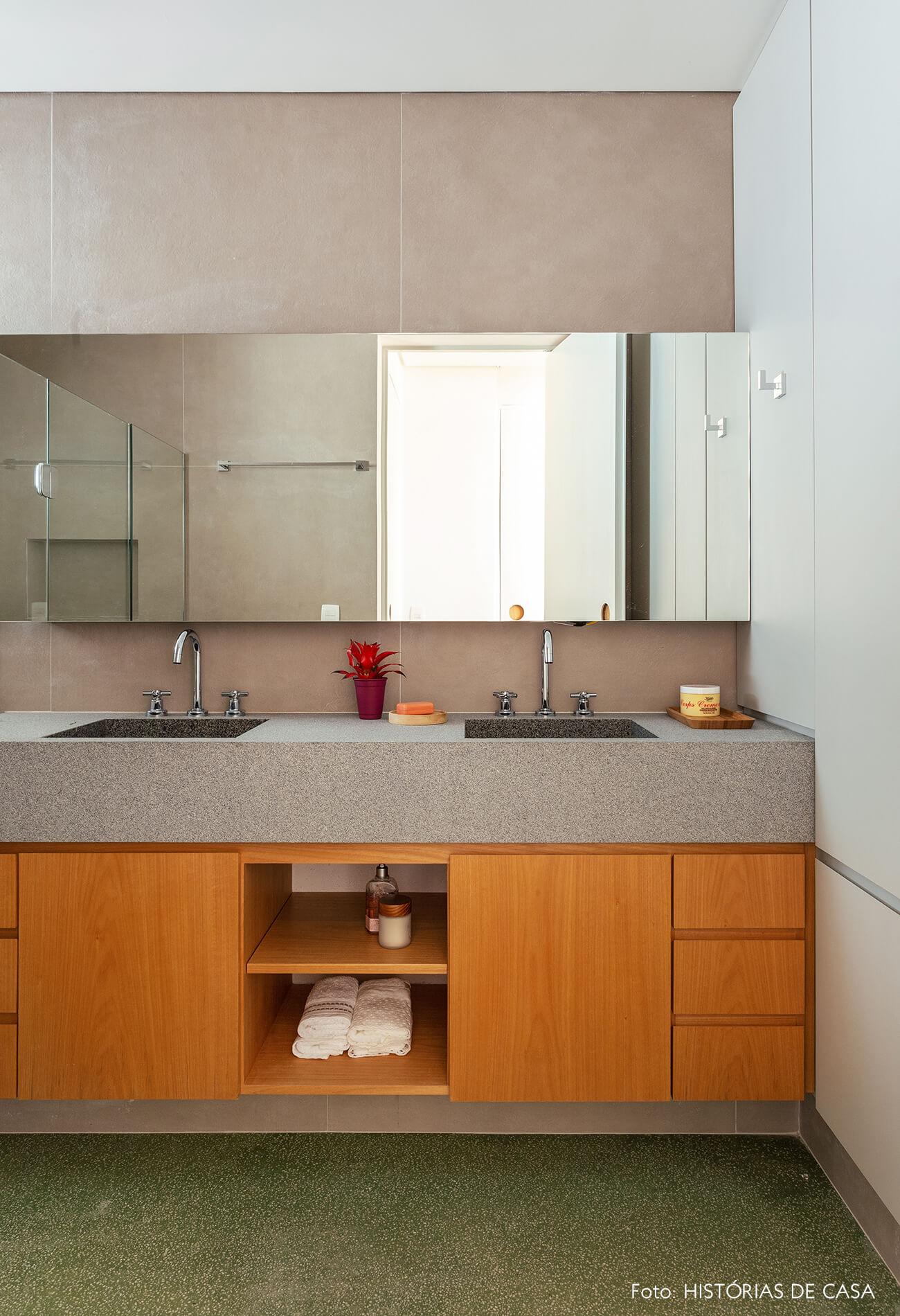 Banheiro com gabinete de marcenaria e piso de granilite verde