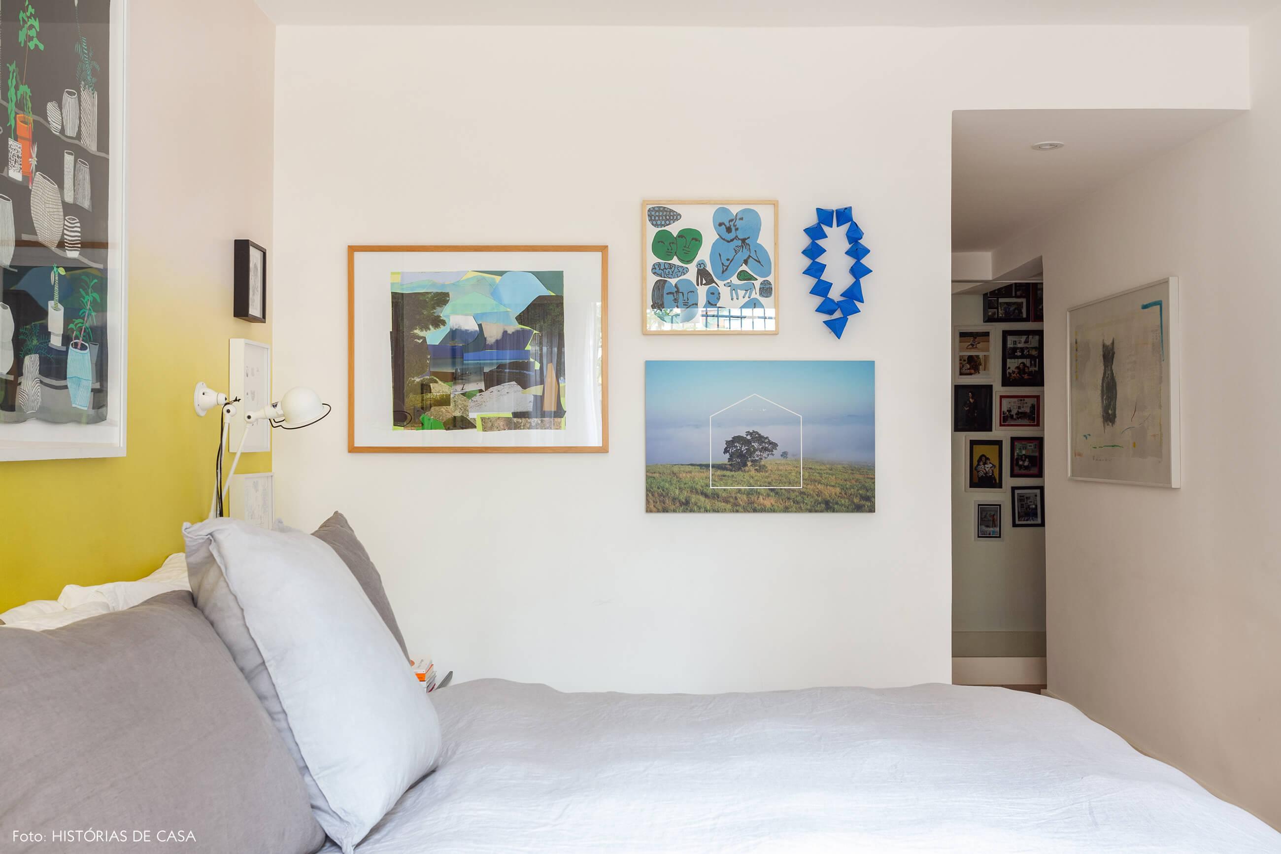 Quarto de casal com papel de parede e parede de quadros azuis