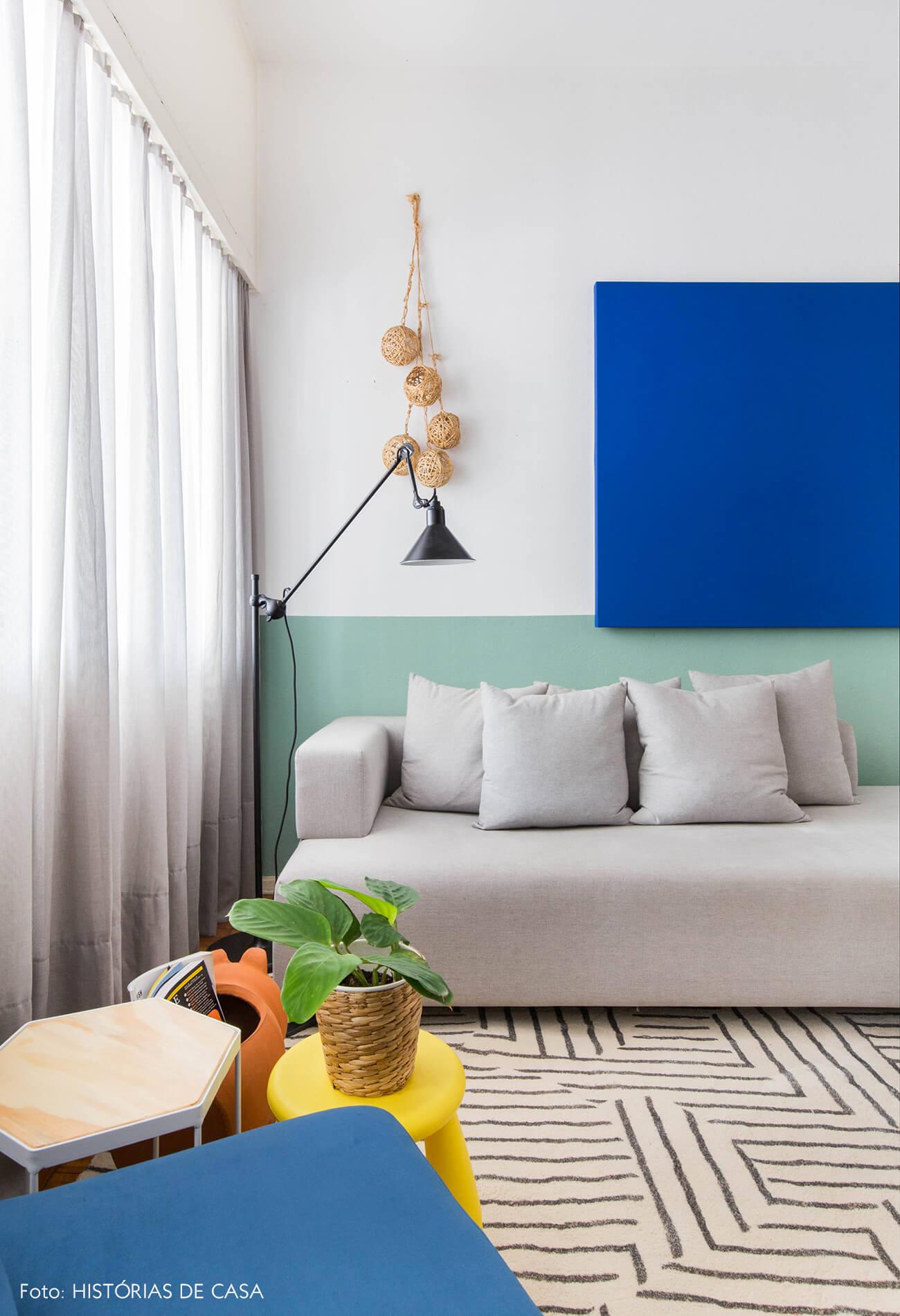 Sala com sofá cinza e meia parede verde