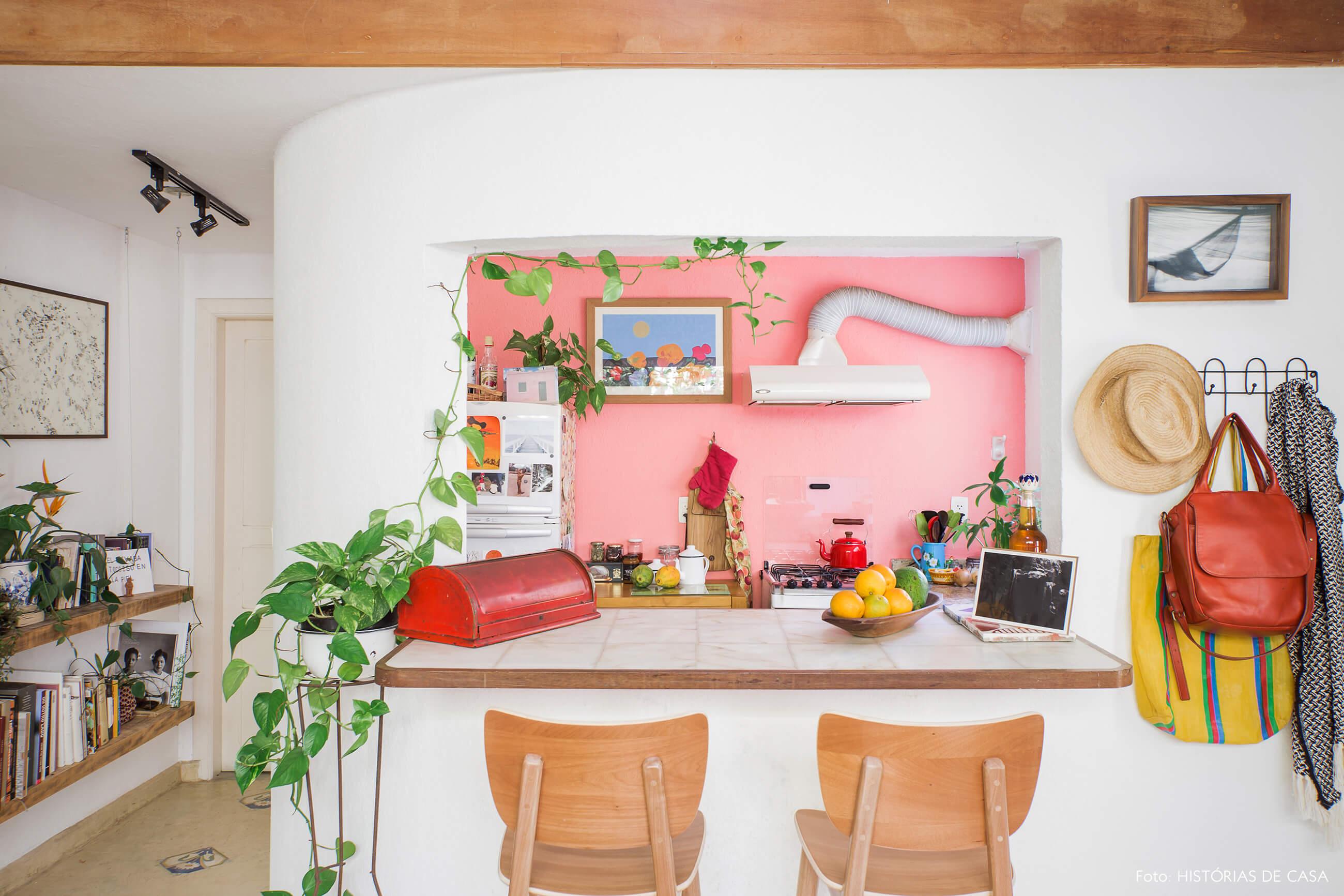 Cozinha americana com balcão e parede colorida