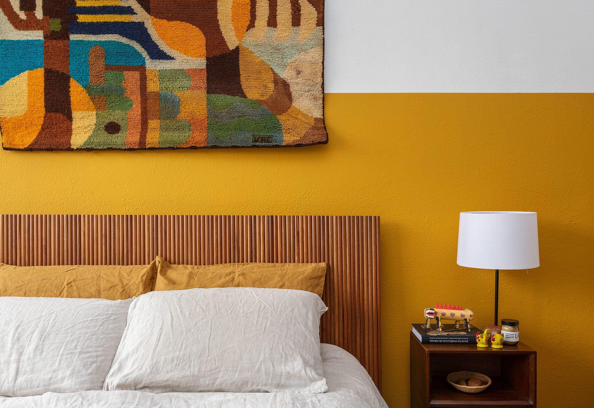 Quarto com parede mostarda e cabeceira de madeira